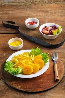 Картофель фри с куриными наггетсами рядом с сырным соусом и кетчупом в соуснике на деревянных досках. вертикальное фото