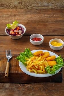 Картофель фри с куриными наггетсами рядом с сырным соусом и кетчупом в соуснике на деревянных досках