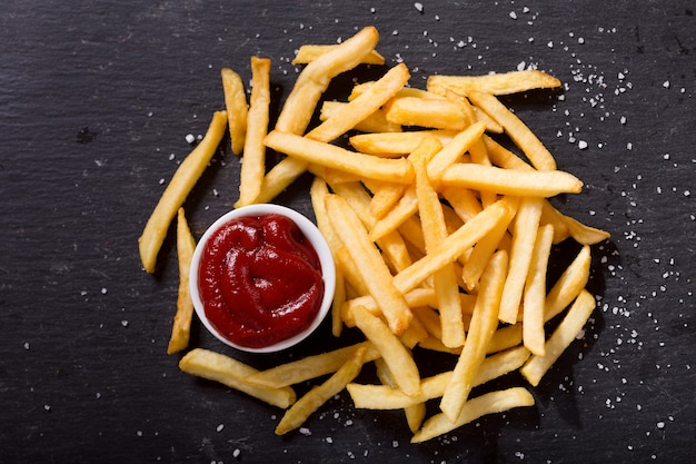 French fries with ketchup on dark background