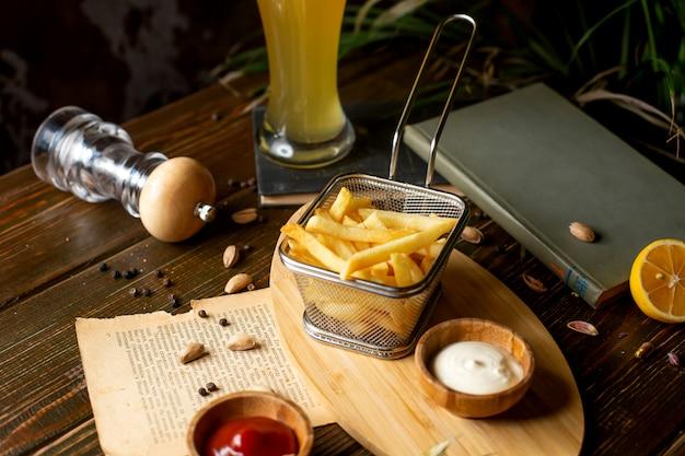 Patate fritte con ketchup e maionese sul tavolo