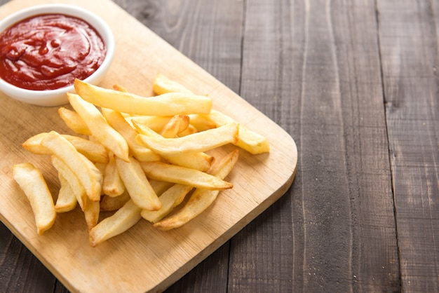 French fries with ketchup on wooden table.