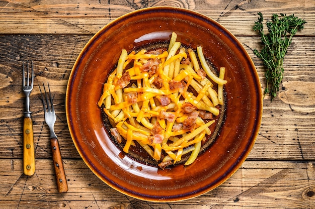 French fries with melted cheddar cheese and bacon served  in a rustic plate. wooden background. top view.