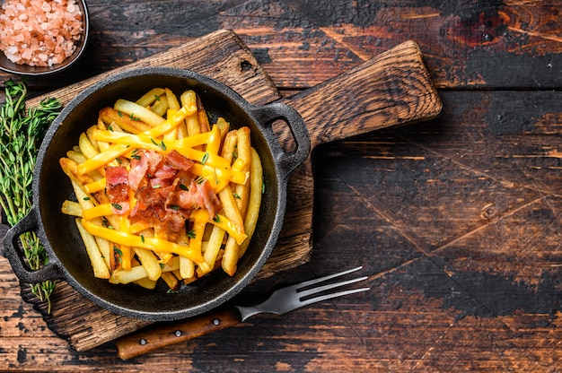 French fries with melted mix of cheddar cheese and bacon served  in a pan. dark wooden background. top view. copy space.