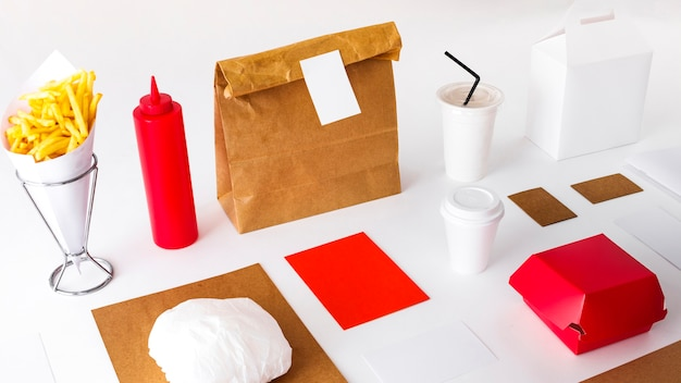French fries with packages and disposal cup on white backdrop