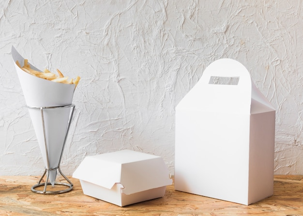 French fries with packages on wooden table