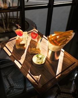 Картофель фри с бутербродами на деревянной тарелке