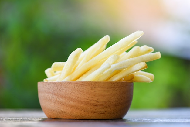 French fries in wooden bowl delicious italian meny homemade ingredients on table nature green background - tasty potato fries for food or snack