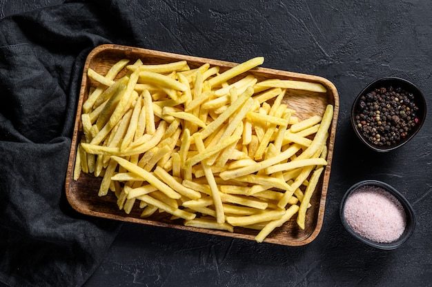 French fries in a wooden bowl. organic potatoes. black background. top view.