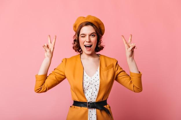 ピースサインを示すフランスの女の子。ピンクの背景に身振りで示す黄色の衣装でスタイリッシュな女性の正面図。
