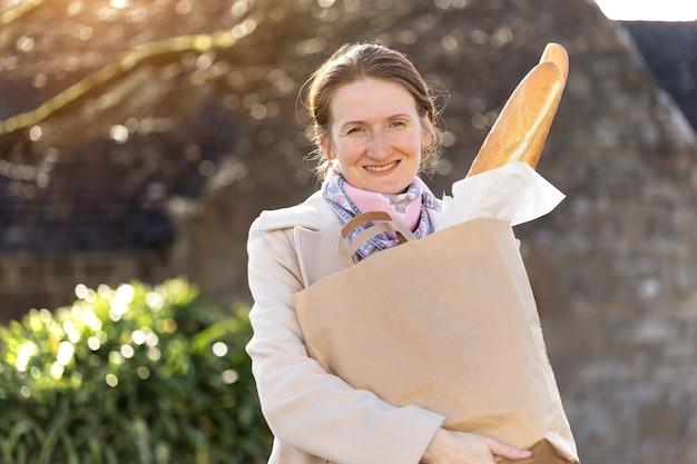 街の通り側にバゲットを持つフランスの女の子