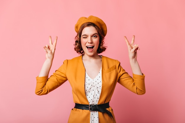 French girl with tattoos showing peace signs. front view of stylish woman in yellow outfit gesturing on pink background.