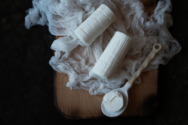 フランスのヤギのチーズ、ソフトチーズ、伝統的な前菜、スナック、デザート、素朴な金属の背景の上にナプキンとセラミックスプーンが付いた木製のサービングボード