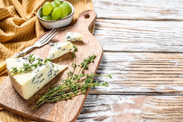 ブドウとフランスのゴルゴンゾーラチーズ。白い木の背景。上面図。スペースをコピーします。
