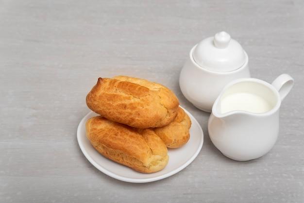 Французские домашние пирожные на блюдце рядом с кувшином для молока. эклеры или профитроли. выпечка. Premium Фотографии