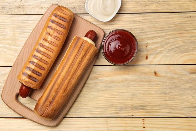 Французские хот-доги. вкусные хот-доги и кетчуп и майонез на натуральном деревянном столе. фаст-фуд уличная еда. сосиски в булочке. вид сверху
