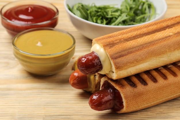 Французские хот-доги. вкусные хот-доги и кетчуп и горчица на натуральном деревянном столе. фаст-фуд уличная еда. сосиски в булочке.