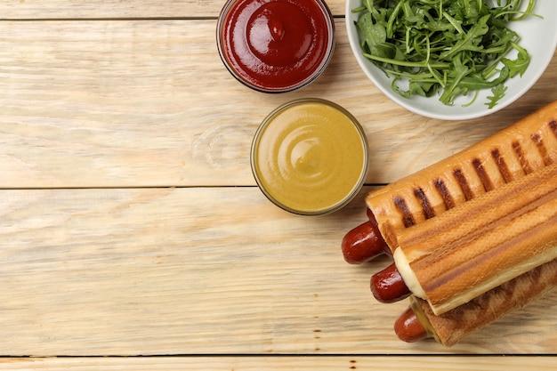 Французские хот-доги. вкусные хот-доги и кетчуп, майонез и горчица на натуральном деревянном столе. фаст-фуд уличная еда. сосиски в булочке. вид сверху