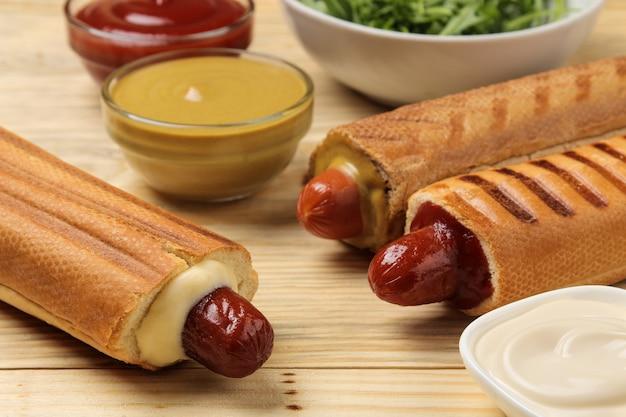 Французские хот-доги. вкусные хот-доги и кетчуп, майонез и горчица на натуральном деревянном столе. фаст-фуд уличная еда. сосиски в булочке.
