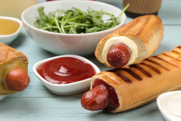Французские хот-доги. вкусные хот-доги и кетчуп на голубом деревянном столе. фаст-фуд уличная еда. сосиски в булочке.