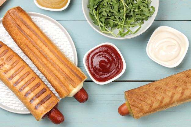 Французские хот-доги. вкусные хот-доги и горчица, майонез, кетчуп на голубом деревянном столе. фаст-фуд уличная еда. сосиски в булочке. вид сверху