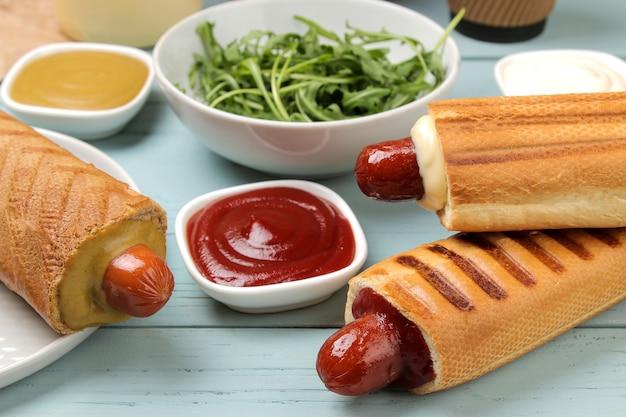 Французские хот-доги. вкусные хот-доги и горчица, майонез, кетчуп на голубом деревянном столе. фаст-фуд уличная еда. сосиски в булочке.