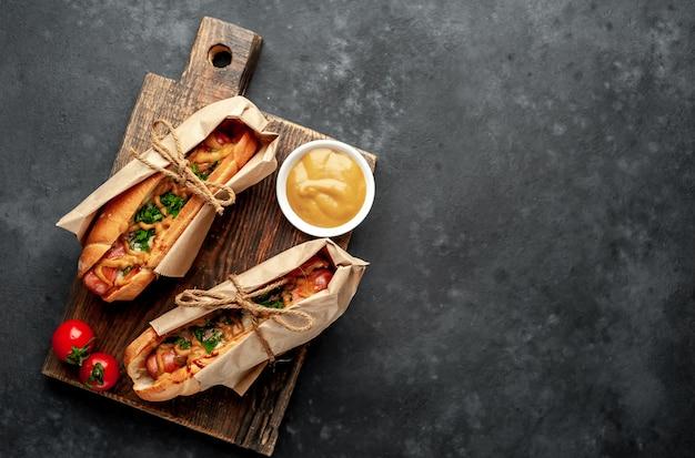 Французские хот-доги из магазина, упакованные в бумагу, запеченные с сыром и горчицей на каменном фоне