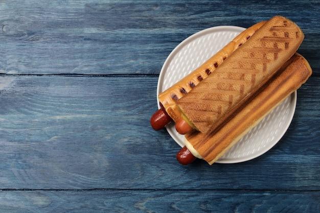 Французские хот-доги. вкусные хот-доги на доске на синем деревянном столе. фаст-фуд уличная еда. сосиски в булочке. вид сверху