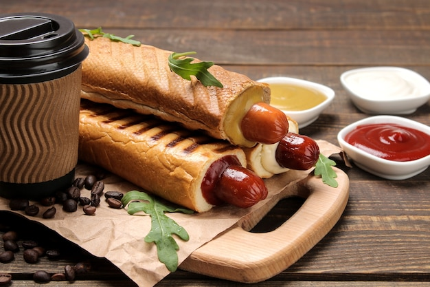 Французские хот-доги. вкусные хот-доги на доске и кофе на коричневом деревянном столе. фаст-фуд уличная еда. сосиски в булочке.