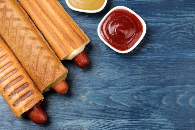 Французские хот-доги. вкусные хот-доги на доске и соус на синем деревянном столе. фаст-фуд уличная еда. сосиски в булочке. вид сверху