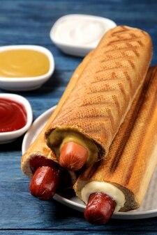 Французские хот-доги. вкусные хот-доги на доске и соус на синем деревянном столе. фаст-фуд уличная еда. сосиски в булочке.