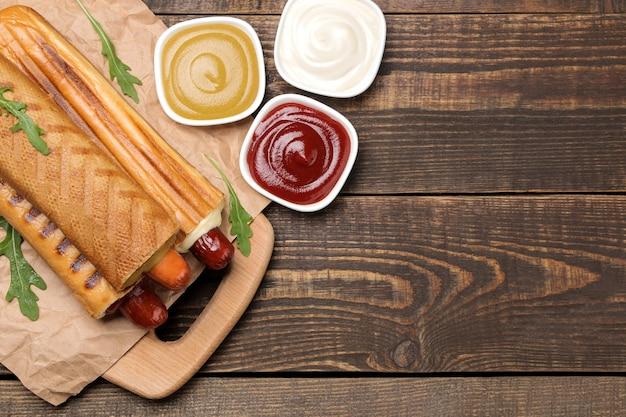 Французские хот-доги. вкусные хот-доги на доске и соус на коричневом деревянном столе. фаст-фуд уличная еда. сосиски в булочке. вид сверху