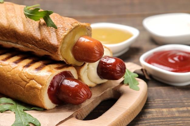 Французские хот-доги. вкусные хот-доги на доске и соус на коричневом деревянном столе. фаст-фуд уличная еда. сосиски в булочке.