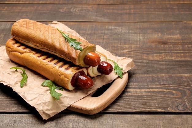 Французские хот-доги. вкусные хот-доги на доске на коричневом деревянном столе. фаст-фуд уличная еда. сосиски в булочке. Premium Фотографии