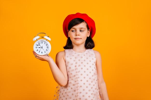 Французский ребенок в стильном берете. кавказский ребенок позирует на желтой стене с часами.