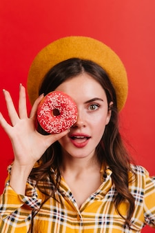 French lady in beret and with red lipstick, covering her face with pink donut.