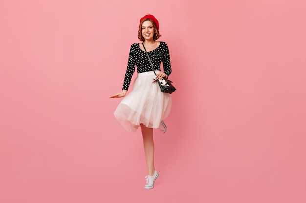 French lady with handbag dancing on pink background. full length view of wonderful girl in red beret and white skirt.