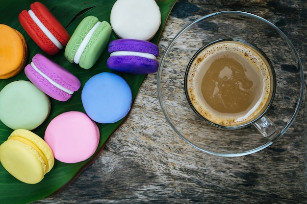 French macaron and cup of hot coffee on wooden table