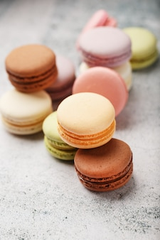 French macaroni cookies of different colors are on the gray table. still life of confectionery.