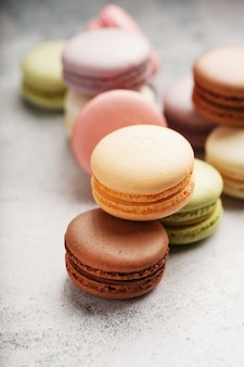 さまざまな色のフレンチマカロニクッキーがグレーのテーブルにあります。菓子の静物。