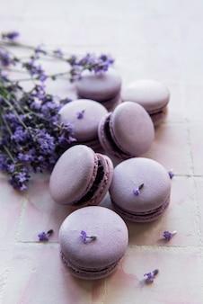타일 배경에 라벤더 향과 신선한 라벤더 꽃이 있는 프랑스 마카롱