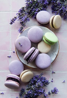 French macarons with lavender flavor and fresh lavender flowers on a  tile background