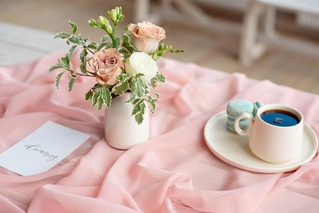 꽃 장미와 녹색 분홍색 식탁보 흰색 꽃병 나무 테이블에 핑크와 커피 컵 서에 프랑스 마 카 롱 블루 접시.