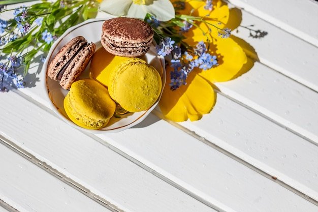 French macaroon sweets and tender flowers blossoms on wooden background.