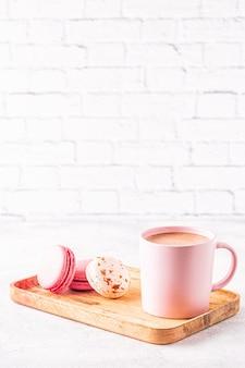 Французские миндальное печенье и чашка кофе на деревянном подносе.