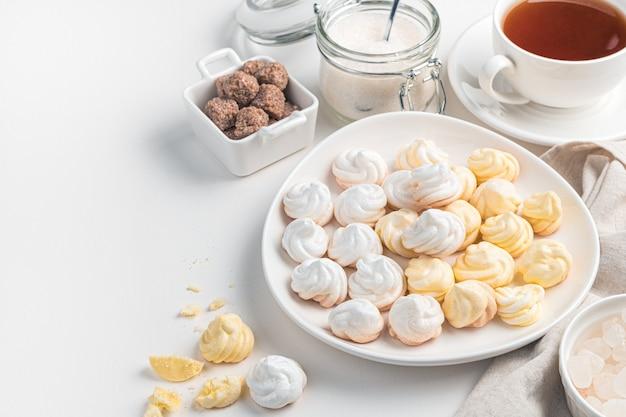 Французские безе желтого и белого цвета на светлом фоне. концепция десертов.