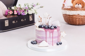 French mousse cake covered with lilac glaze on table.