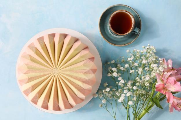 Французский муссовый торт с чашкой чая на блюдце и букетом цветов к празднику