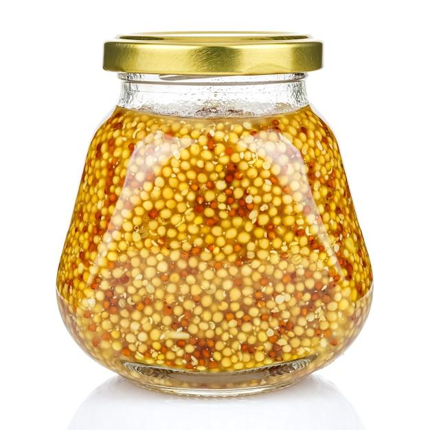 白い背景で隔離の閉じた金色の金属の蓋とピラミッドの透明なガラスの瓶にフレンチマスタード