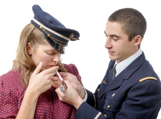Французский офицер закуривает сигарету молодой девушки в стиле ретро