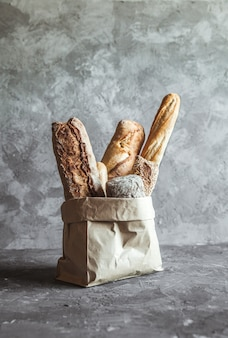 French pastries, baguettes on a gray in a paper bag.